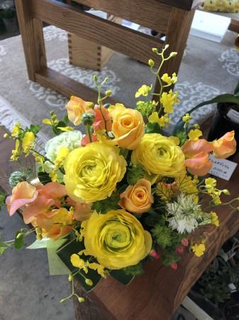 黄色のラナンキュラス、オレンジのスイートピー、ニゲラなどを入れたアレンジメント。